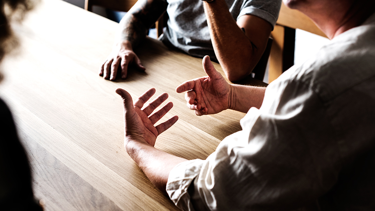 Tres personas hablan alrededor de una mesa / RAWPIXEL.COM