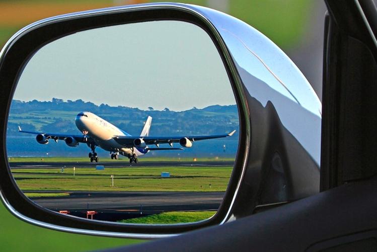 Un avión a punto de despegar visto desde el retrovisor de un coche / PIXABAY