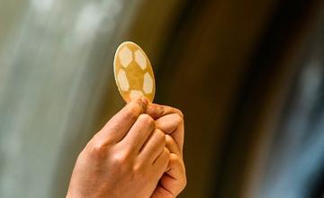 Un sacerdote bendice una hostia con el dibujo de un balón de fútbol / FOTOMONTAJE DE PdF