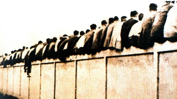 Aficionados del Barcelona sentados en el muro del campo de la calle Indústria, dejando sus culos a la vista, lo que dio origen a los culés / FCBARCELONA